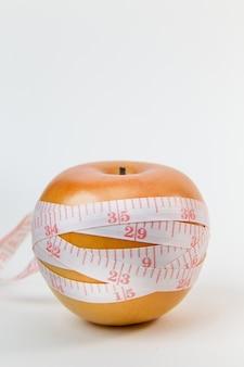 Apple & ruban à mesurer sur fond blanc.
