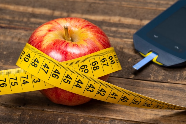 Apple avec ruban à mesurer, symbolisant le surpoids