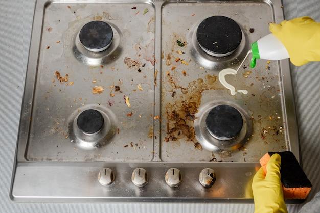 Application de détergent sur la surface de la cuisinière à gaz.