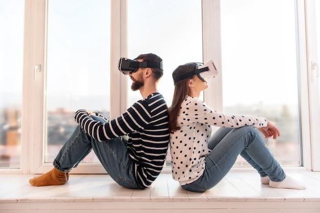 Applications vr. concentré beau couple positif assis sur le rebord de la fenêtre tout en utilisant des casques vr et en profitant de la technologie
