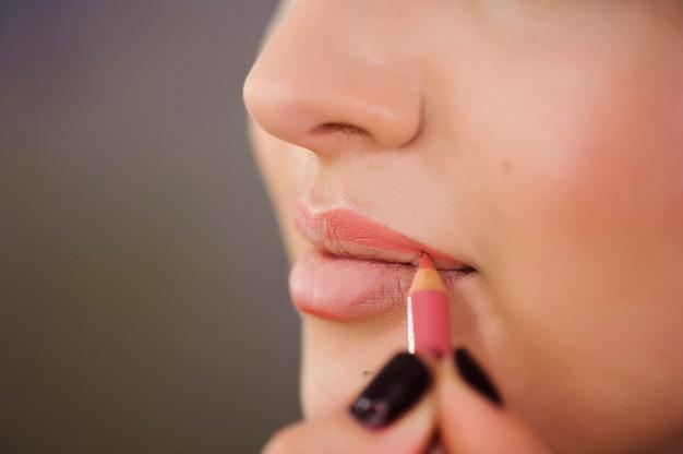 Appliquer le contour des lèvres. gros plan du visage de femme. cosmétiques de beauté, concept de maquillage.