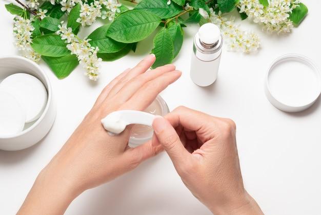Appliquer la crème pour les mains avec une spatule en plastique en prenant un tableau blanc crème avec une cerise d'oiseau