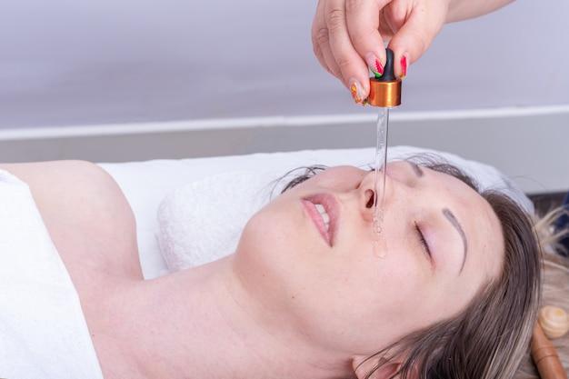 Appliquer de l'huile essentielle à la pipette sur le visage de la fille pour masser le visage et le cou. massage anti-âge visage et cou. soins cosmétiques pour la peau du visage et du cou