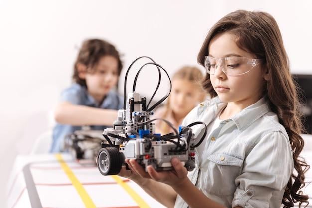 Appliquer mes connaissances. fille intelligente qualifiée impliquée debout à l'école et tenant un robot pendant que des collègues travaillant sur le projet