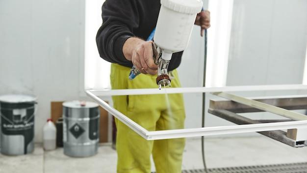 Apporter l'innovation à la surface, l'homme tient un vaporisateur aérographe pour la peinture et la teinture