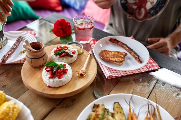 Appréciant le dîner, l'homme mange, la table du dîner, la variété d'apéritifs servant sur la table extérieure de la fête à la maison.
