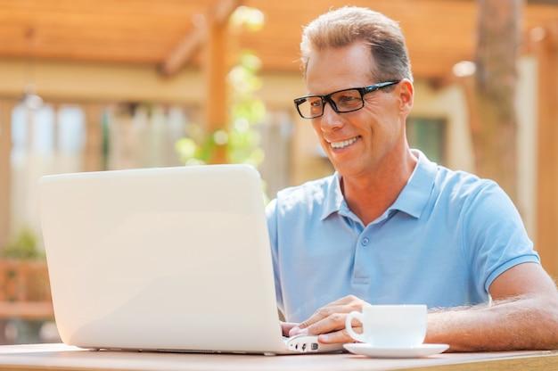 Apprécier son travail sur l'air frais. homme mûr gai travaillant à l'ordinateur portable et souriant tout en s'asseyant à la table dehors avec la maison à l'arrière-plan