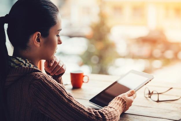 Apprécier le travail et l'air frais. vue latérale d'une belle jeune femme tenant une tablette numérique alors qu'elle était assise à la table en bois brut