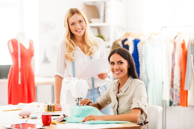 Apprécier le travail créatif ensemble. deux jeunes femmes gaies travaillant ensemble dans leur atelier de mode
