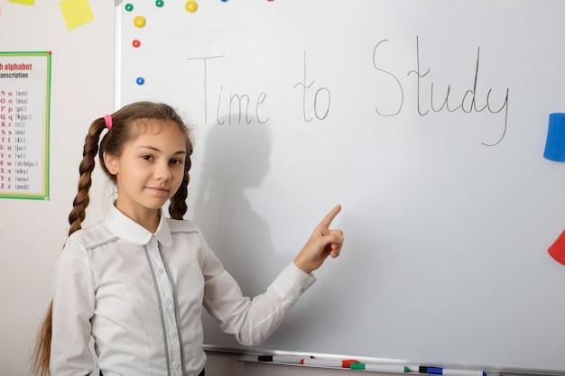 Apprenant de l'école adolescente caucasienne pointant vers le tableau avec le temps d'inscription pour étudier