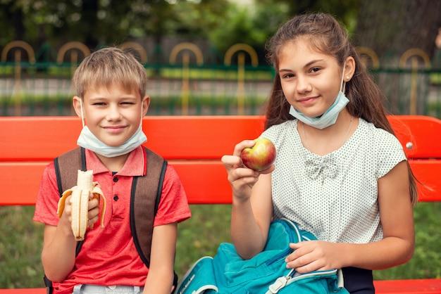 Les apprenants de l'école dans des masques médicaux assis sur le banc dans la cour d'école ayant une collation pendant une pause