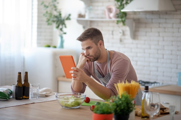 Apprendre à cuisiner. un homme essayant de préparer une salade avec des tutoriels en ligne