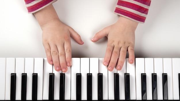 Apprendre un instrument de musique, la main de l'enfant sur les touches du piano.