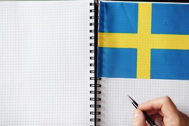 Apprendre des langues étrangères. bloc-notes pour les entrées et un drapeau. cours de langues, audition audio.