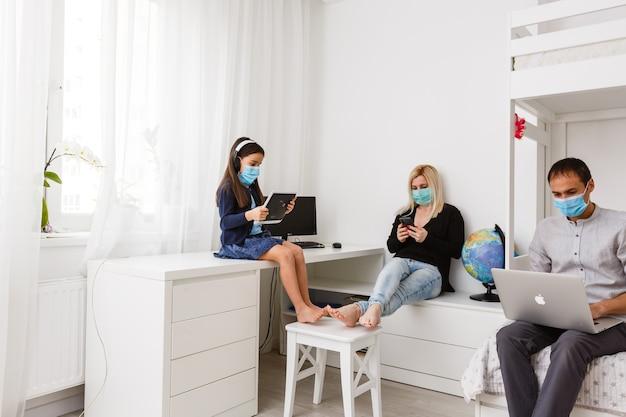 Apprendre à la maison, apprentissage en ligne, concept d'auto-quarantaine. famille à la maison. enfants faisant leurs devoirs et parents travaillant en ligne