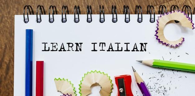 Apprenez le texte italien écrit sur un papier avec des crayons au bureau