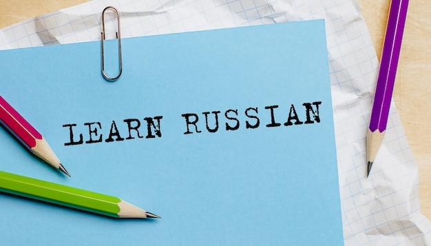 Apprenez le texte russe écrit sur un papier avec des crayons au bureau