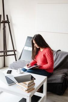 Apprentissage à distance. e-learning. jeune femme latine enseignant l'anglais en ligne à l'aide d'un ordinateur portable assis sur le canapé