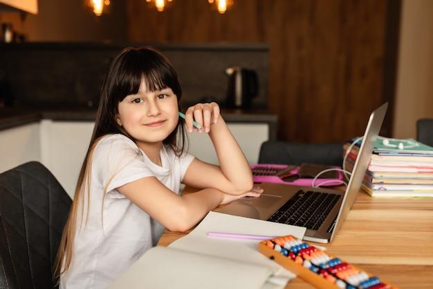 Apprentissage en ligne à domicile. écolière heureuse, concept d'éducation à distance