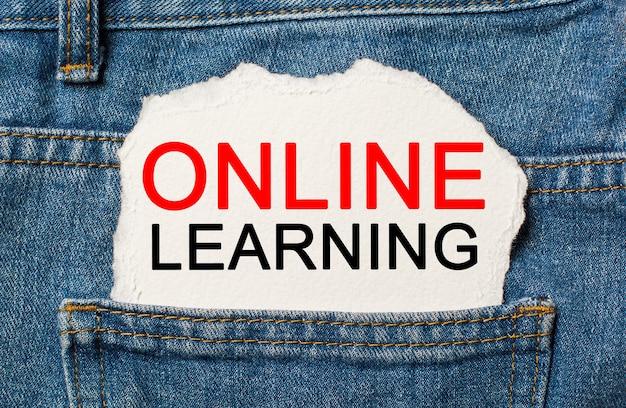 Apprentissage en ligne sur fond de papier déchiré sur le concept d'étude et d'éducation des jeans