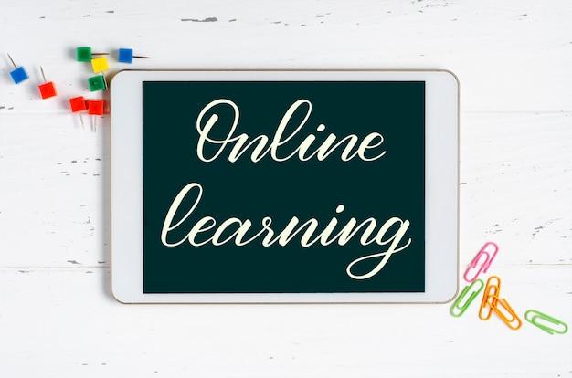 Apprentissage en ligne - inscription manuscrite sur une tablette. le concept de formation à distance pour les enfants. tablette et fournitures de bureau sur un fond en bois blanc.