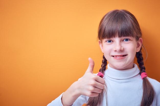 Approbation et consentement, adolescente caucasienne montre le pouce vers le haut sur coloré