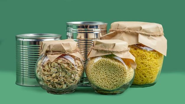 Approvisionnement alimentaire pendant la quarantaine des coronavirus et l'auto-isolement. livraison de nourriture, don, soutien bénévole. aliments en conserve, pâtes et céréales sur fond vert.