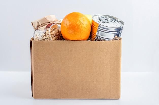Approvisionnement alimentaire pendant la quarantaine des coronavirus et l'auto-isolement. livraison de nourriture, don, soutien bénévole. boîte en carton avec divers aliments en conserve, pâtes et céréales. emballage écologique.