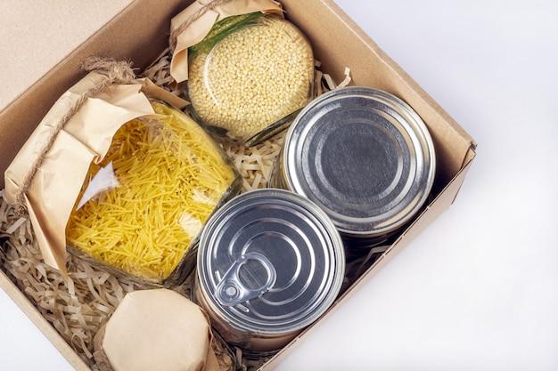 Approvisionnement alimentaire pendant la quarantaine des coronavirus et l'auto-isolement. livraison de nourriture, don, soutien bénévole. boîte en carton avec divers aliments en conserve, pâtes et céréales.