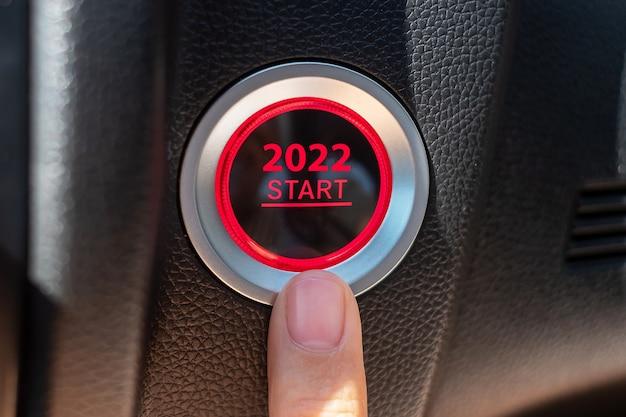 Appuyez avec le doigt sur un bouton d'allumage de voiture avec le texte start 2022