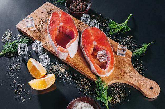Appuyez sur les steaks de poisson aux épices, au citron et aux herbes sur un fond sombre.