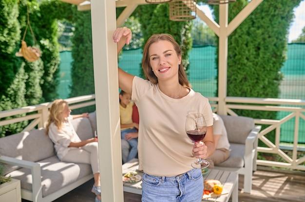 Après le dîner. une femme souriante debout avec un verre de vin dans les mains