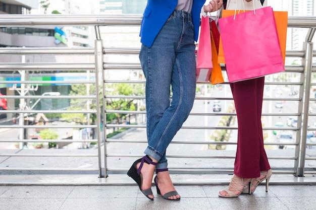 Après la journée de shopping. closeup, jeune, femme, porter, sacs provisions, tout, marcher long, rue