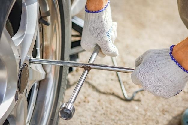 Après une panne, une personne change une roue d'une voiture pour une autre roue avec une clé