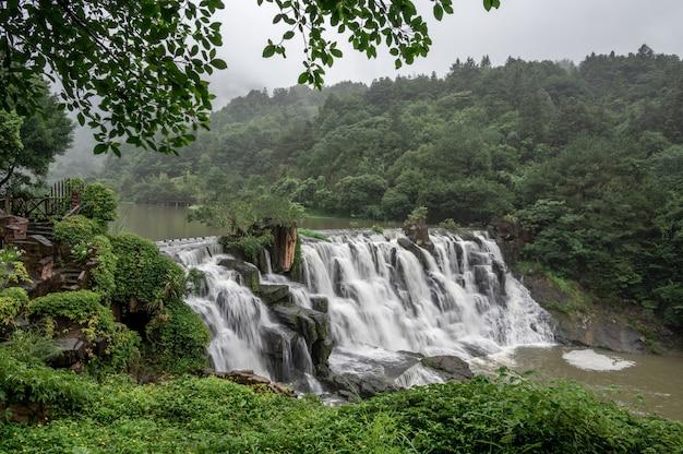 Après la pluie, la cascade devant le rocher est plus grande