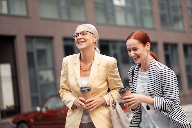 Après le travail. deux femmes d'affaires prospères portant leurs tasses de café en papier en riant et en marchant le long de la rue