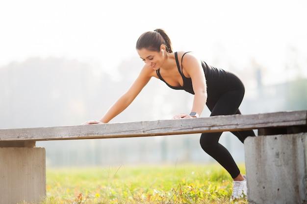Aptitude. femme athlétique debout en position de planche à l'extérieur au coucher du soleil. concept du sport, des loisirs et de la motivation
