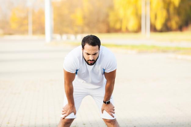 Aptitude. homme fatigué coureur reste après avoir couru sur la ville stree
