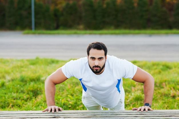 Aptitude. homme de remise en forme exercice fitness bras muscles au gym en plein air