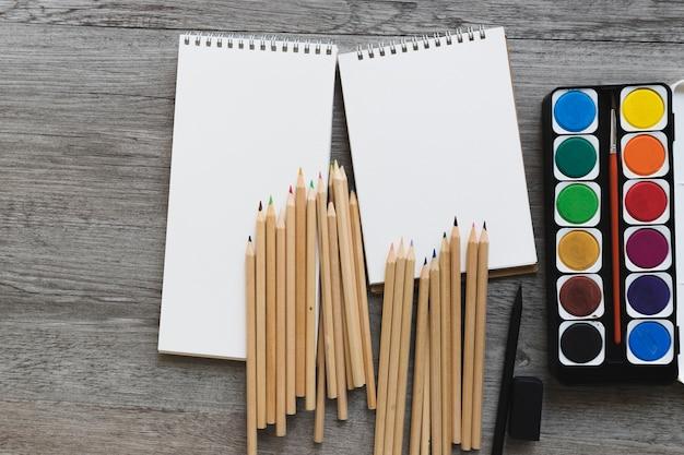 Aquarelle et crayons près des carnets de croquis