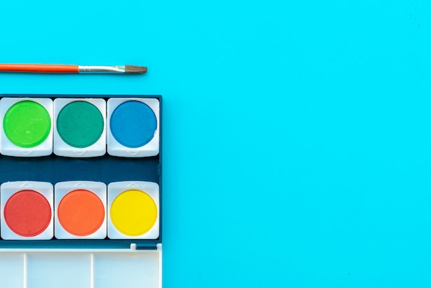 Aquarelle et pinceau posés sur la table de peinture