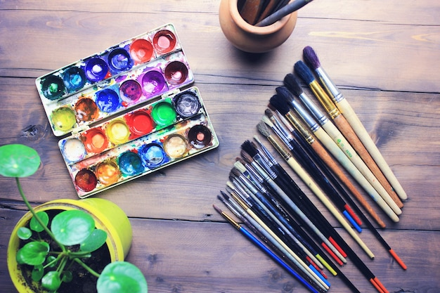 Aquarelle et pinceaux sur fond de table en bois
