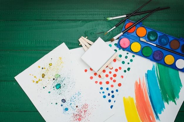 Aquarelle tachée et coups de pinceau sur une feuille blanche avec mini palette de chevalet et aquarelle