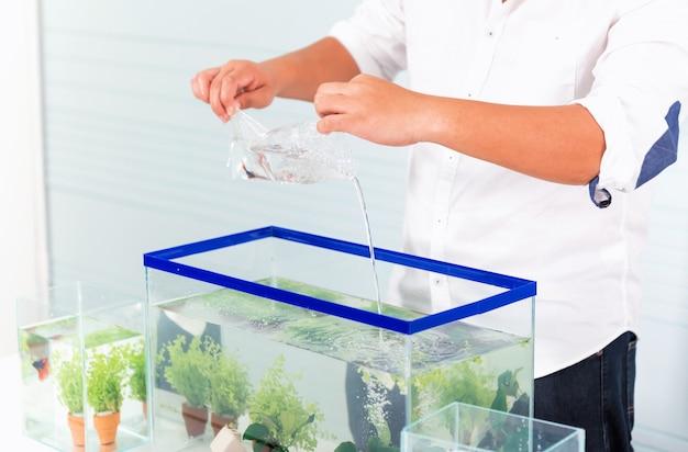 Aquarium pour animal de compagnie et passe-temps à la maison. tenir un sac en plastique avec du nouveau poisson.