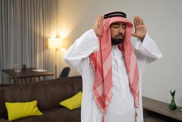 Un arabe dans un turban prie pendant le mouvement takbir à deux mains