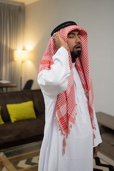 Un arabe en turban priant pendant le mouvement takbir