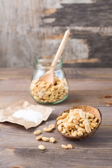 Arachides salées dans un bol et dans un bocal avec une cuillère et du sel sur papier sur une table en bois. nourriture végétarienne saine. style rustique. vue verticale