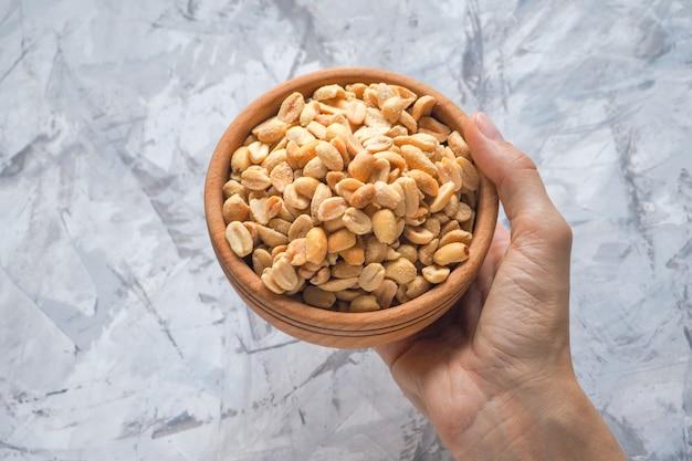 Arachides salées grillées à la main. noix grillées dans un bol.