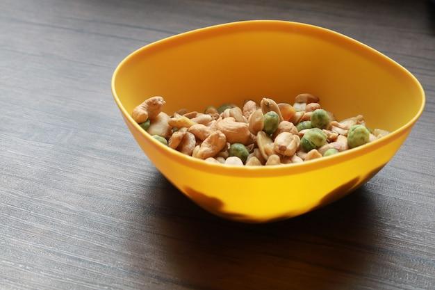 Arachides séchées mélangées noix de cajou et noix dans le bol jaune mis sur la table en bois fond snack pour végétarien