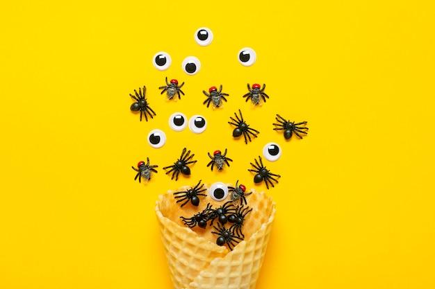 Des araignées et des mouches noires, des yeux écarquillés sortent du cornet de crème glacée. vue de dessus plat